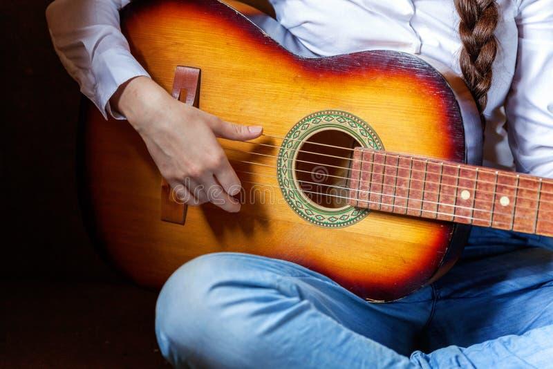 Mujer joven que toca la guitarra imagen de archivo