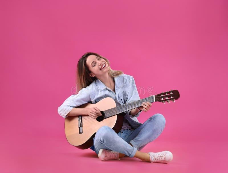 Mujer joven que toca la guitarra acústica fotografía de archivo libre de regalías