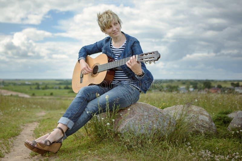 Mujer joven que toca la guitarra que se sienta en roca en el campo en tiempo ventoso imagen de archivo