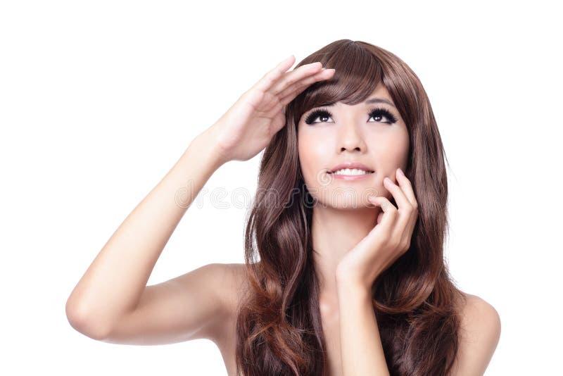 Mujer joven que toca su cara y que mira para arriba foto de archivo libre de regalías