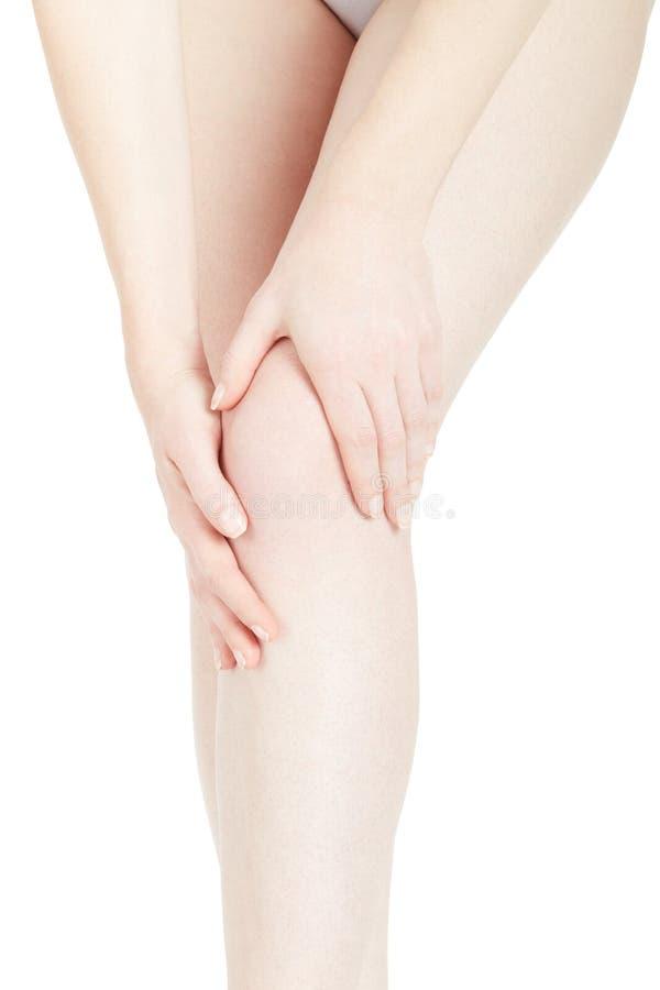 Mujer joven que toca su dolor de la rodilla de la sensación de la pierna en blanco imágenes de archivo libres de regalías