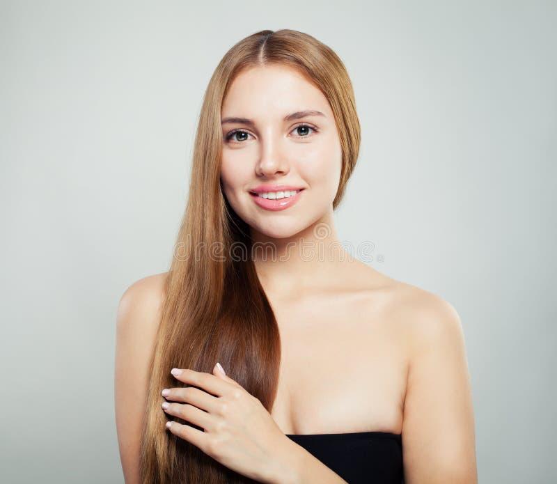 Mujer joven que toca su mano su pelo Muchacha perfecta con el pelo sano natural y el retrato claro de la piel imagenes de archivo