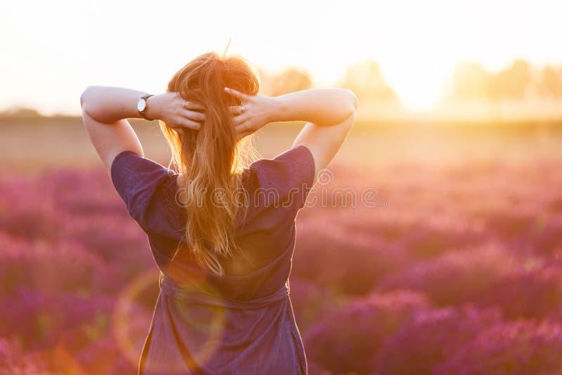 Mujer joven que toca su pelo sombrío largo que mira el campo de la lavanda la puesta del sol imagenes de archivo