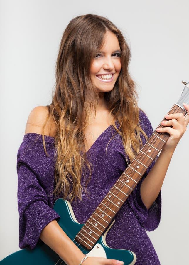 Mujer joven que toca una guitarra eléctrica fotografía de archivo