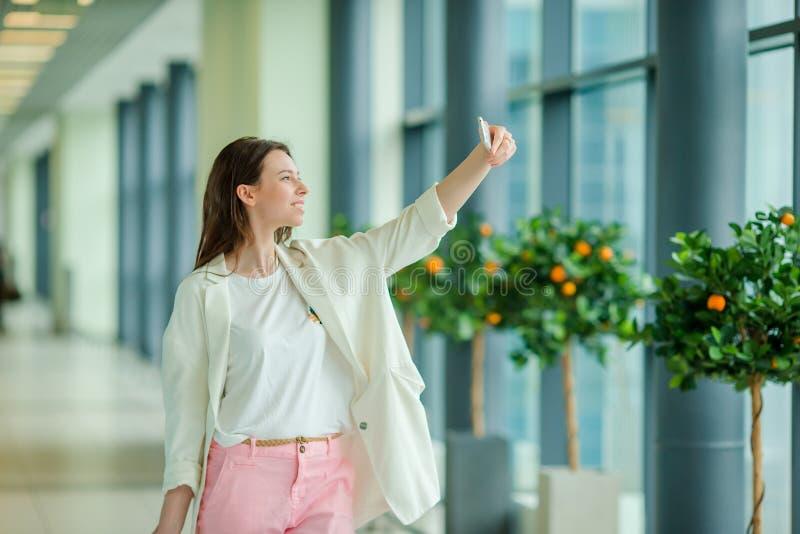 Mujer joven que toma el seldie por smartphone en vuelo que espera del aeropuerto internacional para imagenes de archivo