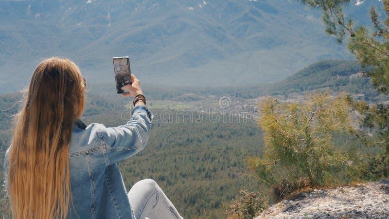 Mujer joven que toma el selfie con el tel?fono m?vil al aire libre fotografía de archivo
