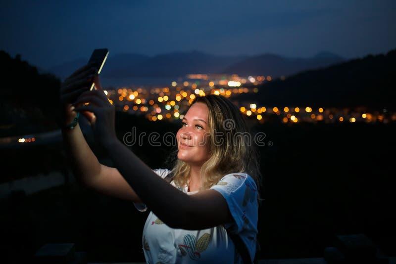 Mujer joven que toma el selfie encima de la colina observando la opinión de la ciudad de la noche Buena luz de la pantalla imagen de archivo libre de regalías