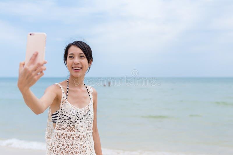 Mujer joven que toma el selfie por el teléfono móvil en playa fotos de archivo libres de regalías