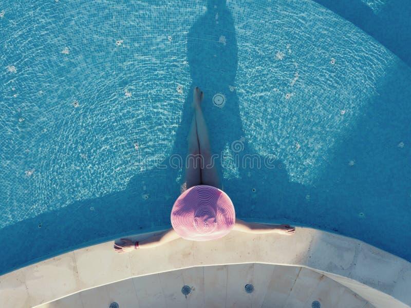 Mujer joven que toma el sol en una piscina imagen de archivo