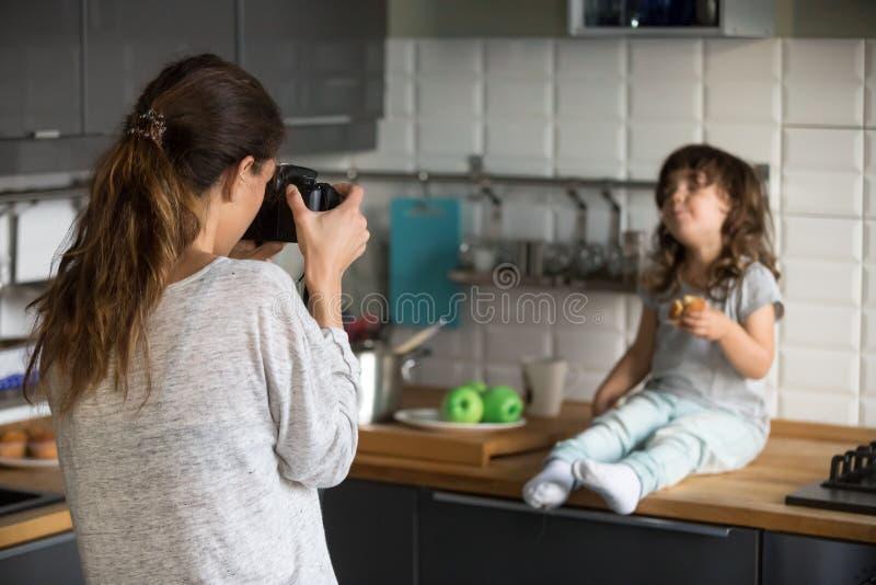 Mujer joven que toma a foto la niña linda en cocina foto de archivo libre de regalías