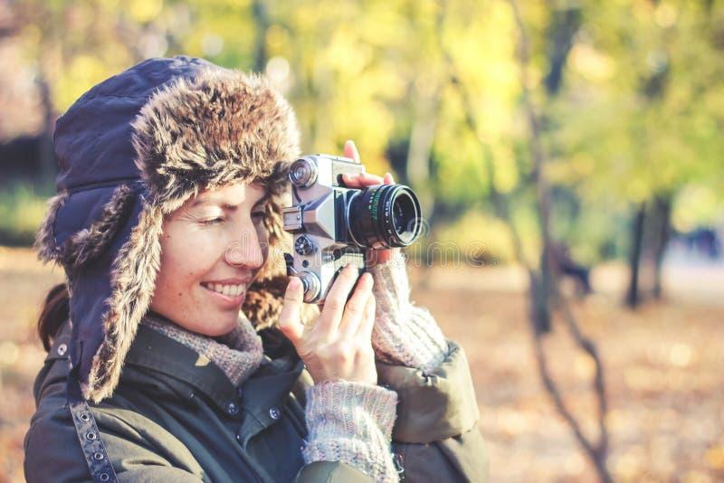 Mujer joven que toma imágenes en el parque del otoño imágenes de archivo libres de regalías