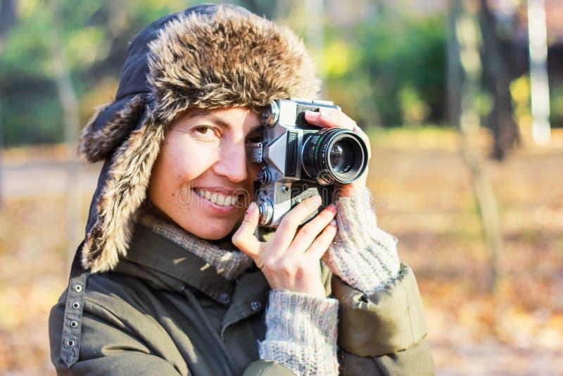 Mujer joven que toma imágenes en el parque del otoño imagen de archivo