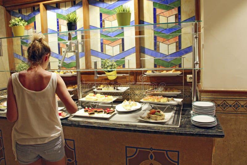 Mujer joven que toma la comida en el buffet del centro tur?stico Todo el inclusivo durante d?as de fiesta foto de archivo