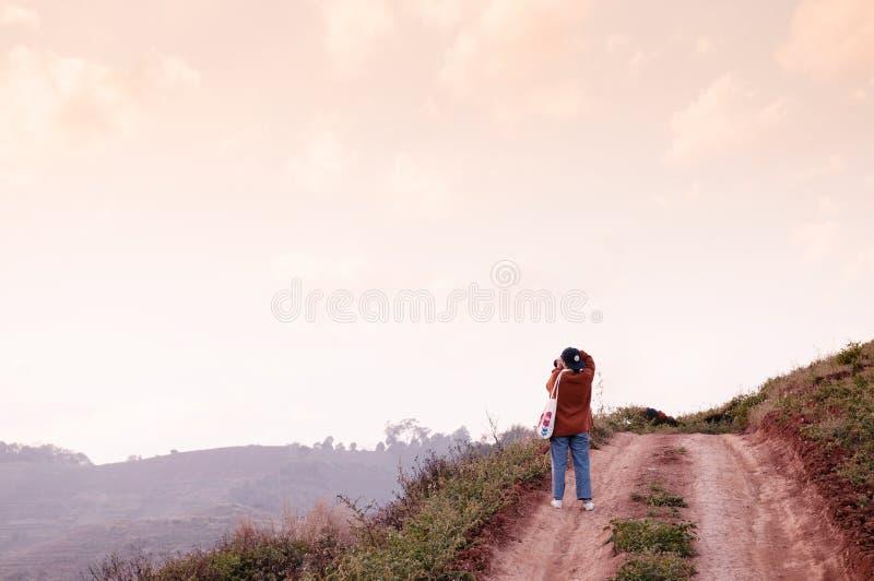 Mujer joven que toma la foto del cielo de la puesta del sol en la carretera nacional de la trayectoria de la suciedad fotografía de archivo