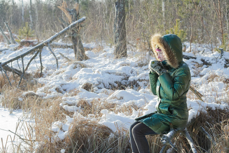 Mujer joven que toma la rotura en bosque nevoso del invierno al aire libre foto de archivo libre de regalías