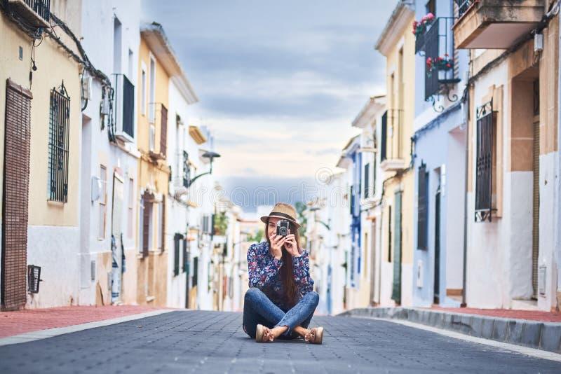 Mujer joven que toma las fotos con la cámara vieja foto de archivo