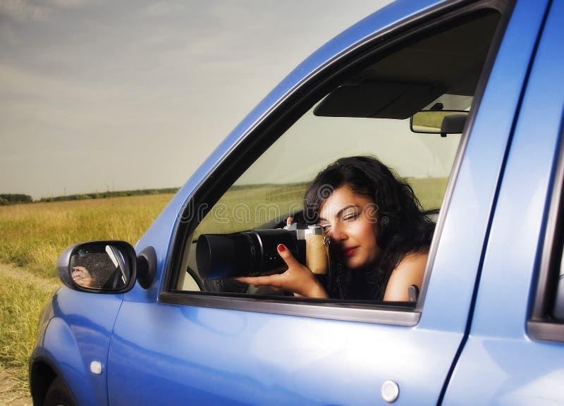 Mujer joven que toma las fotos con la lente de telephoto imagen de archivo libre de regalías