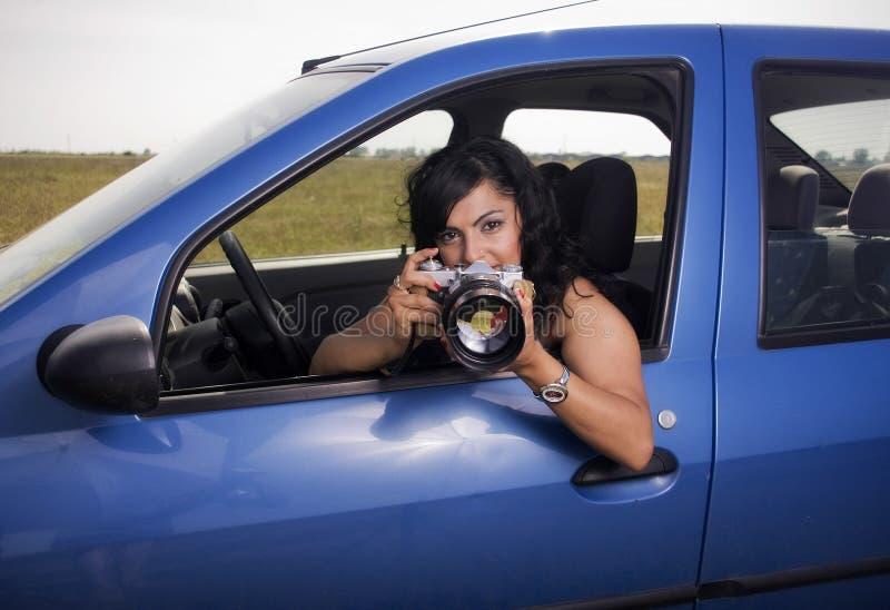Mujer joven que toma las fotos con la lente de telephoto fotos de archivo