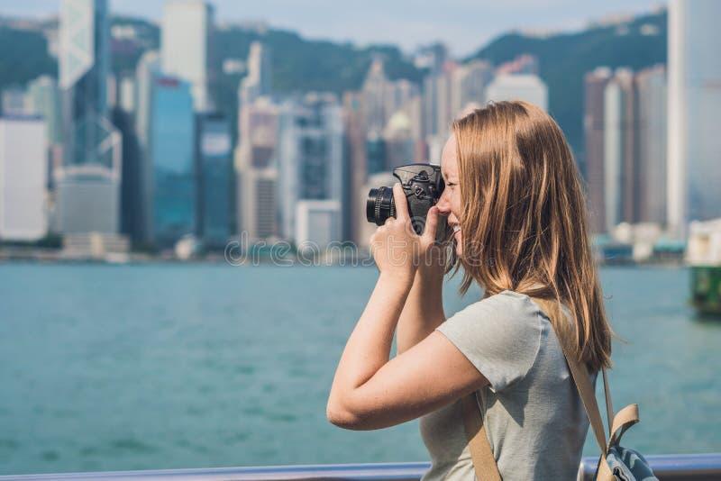 Mujer joven que toma las fotos del puerto de Victoria en Hong Kong, China imagen de archivo libre de regalías
