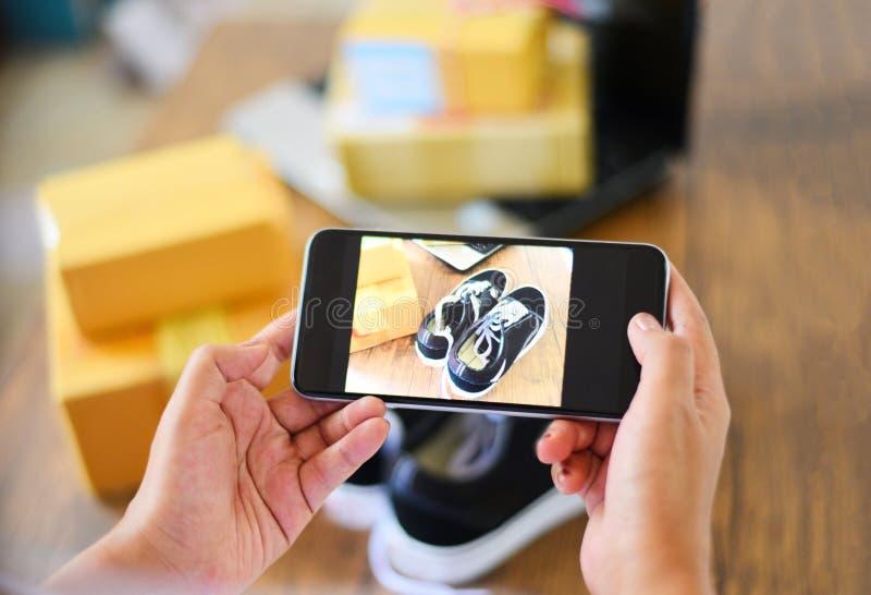 Mujer joven que toma las zapatillas de deporte de la foto con el smartphone de la cámara para que poste venda en línea en la pági imagen de archivo