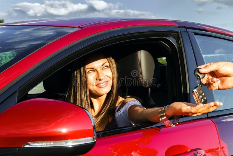 Mujer joven que toma llaves del nuevo coche imagen de archivo libre de regalías