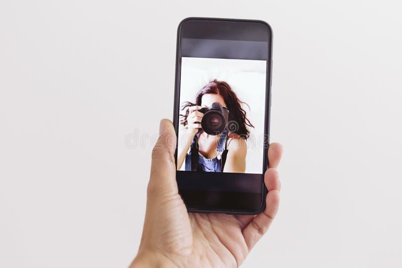 Mujer joven que toma un autorretrato en la cámara delantera del teléfono móvil en casa Paredes y fondo blancos Cubierta de la cám fotos de archivo