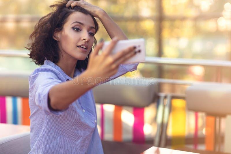 Mujer joven que toma un selfie en cafetería imagen de archivo libre de regalías
