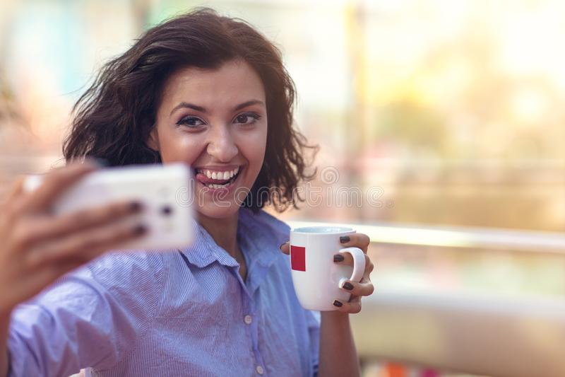 Mujer joven que toma un selfie en cafetería imágenes de archivo libres de regalías