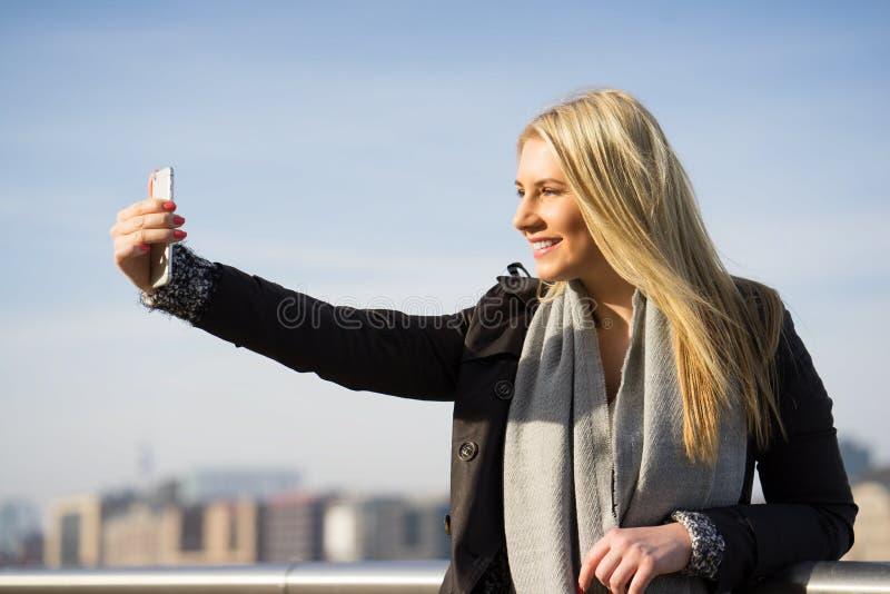 Mujer joven que toma un selfie en el sol del otoño imagenes de archivo
