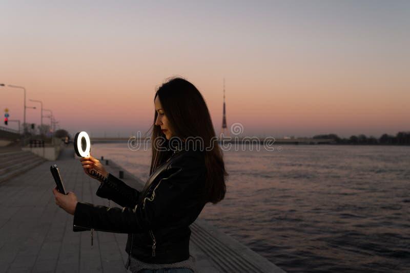 Mujer joven que toma un selfie usando un flash del anillo como luz del terraplén en una puesta del sol con una visión sobre Dau imagen de archivo libre de regalías