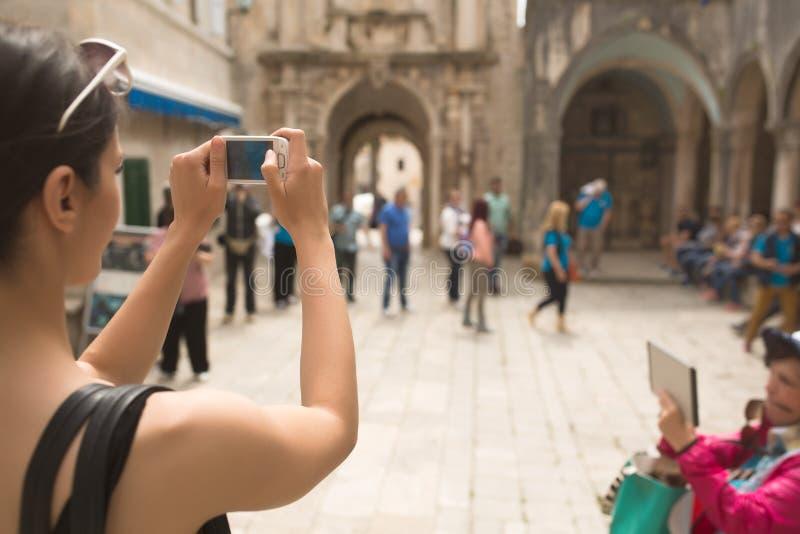 Mujer joven que toma una foto con su smartphone Turista de la mujer que captura memorias Viaje turístico alrededor de la ciudad V imagenes de archivo