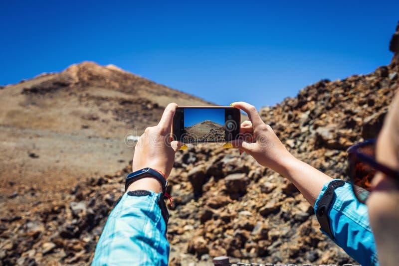 Mujer joven que toma una foto con su teléfono de las montañas asombrosas l foto de archivo