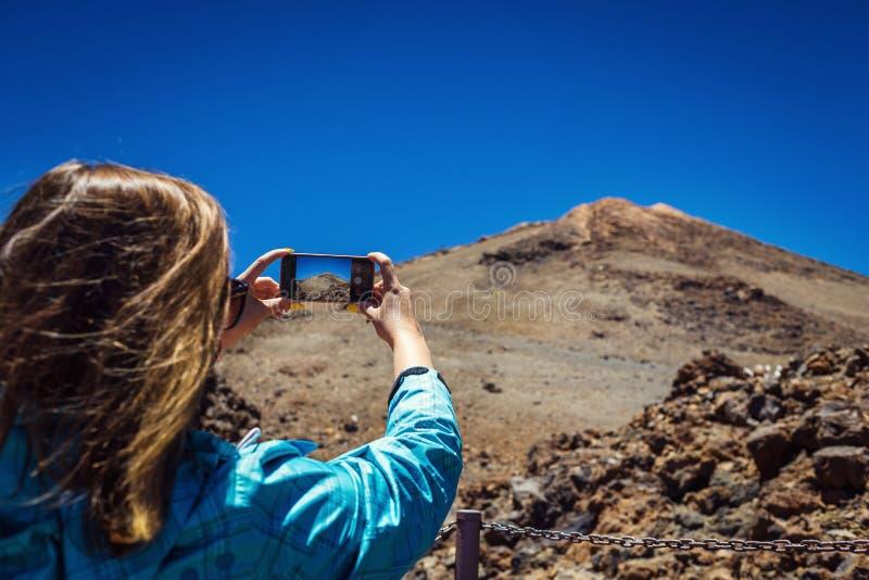 Mujer joven que toma una foto con su teléfono de las montañas asombrosas l fotografía de archivo