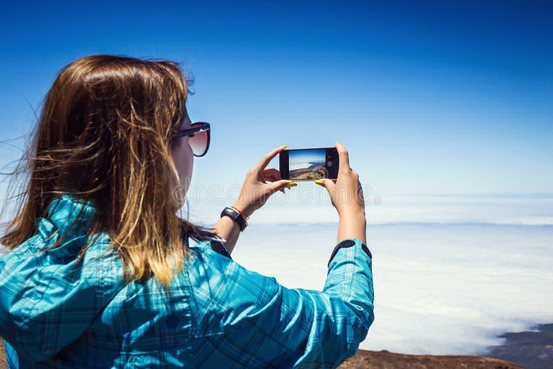 Mujer joven que toma una foto con su teléfono de las montañas asombrosas l imagen de archivo