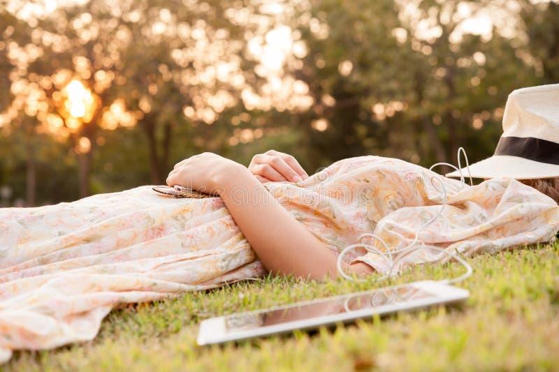 Mujer joven que toma una siesta en parque con el sombrero sobre cara con la tableta imagen de archivo