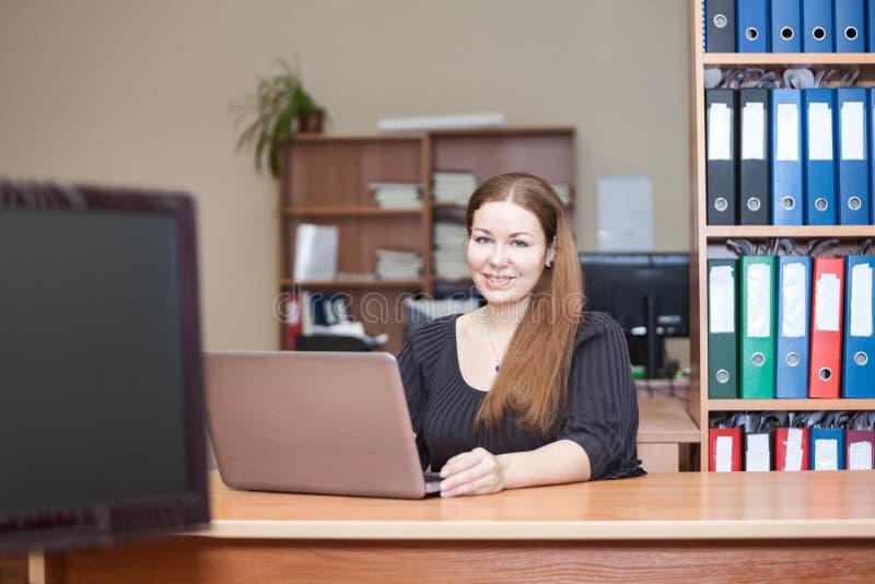Mujer joven que trabaja con el ordenador portátil en oficina foto de archivo libre de regalías