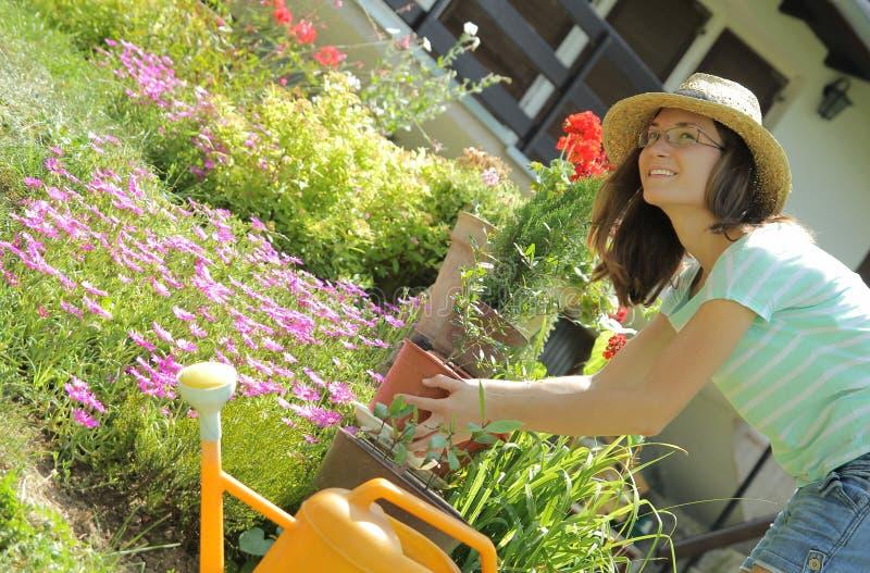 Mujer joven que trabaja con las flores en el jardín foto de archivo libre de regalías