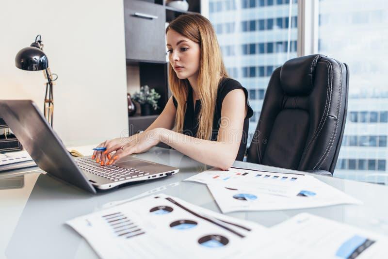 Mujer joven que trabaja en el ordenador port?til que estudia datos financieros y las estad?sticas de la compa??a imagen de archivo libre de regalías