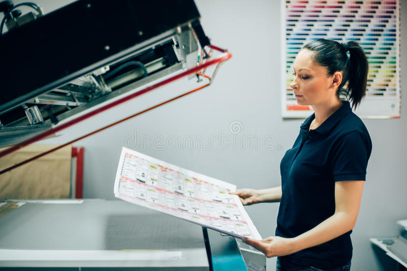 Mujer joven que trabaja en fábrica de la impresión foto de archivo libre de regalías