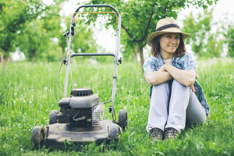 Mujer joven que trabaja en hierba del ajuste del jardín con el cortacésped imagenes de archivo