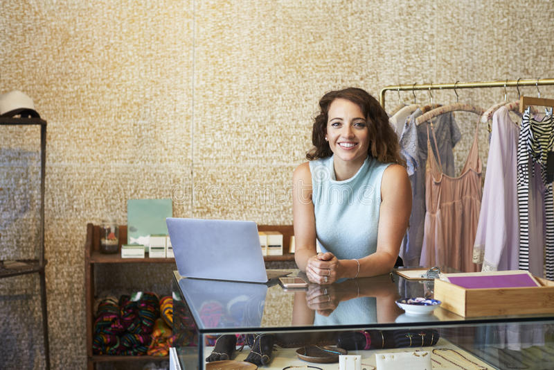Mujer joven que trabaja en la tienda de ropa que se inclina en contador imagenes de archivo