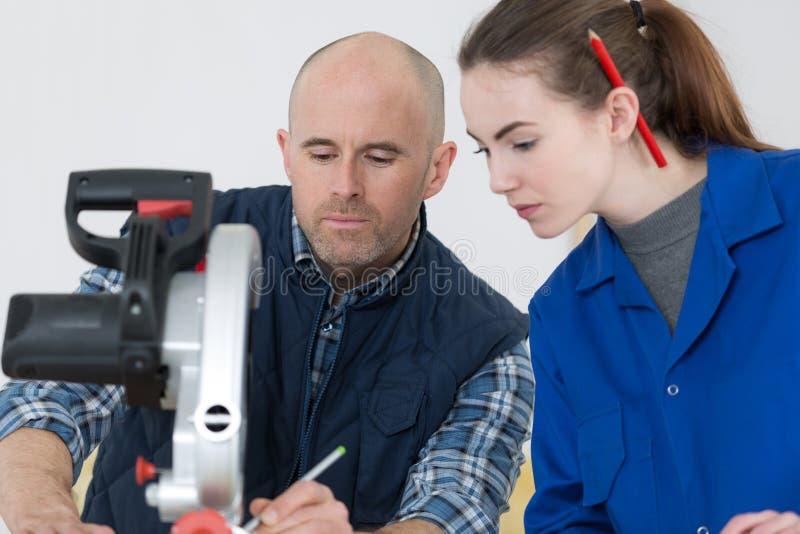 Mujer joven que trabaja en la tienda del carpintero con el profesor fotos de archivo