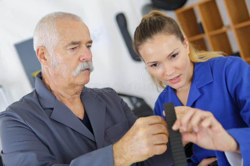 Mujer joven que trabaja en la tienda del carpintero con el profesor imágenes de archivo libres de regalías