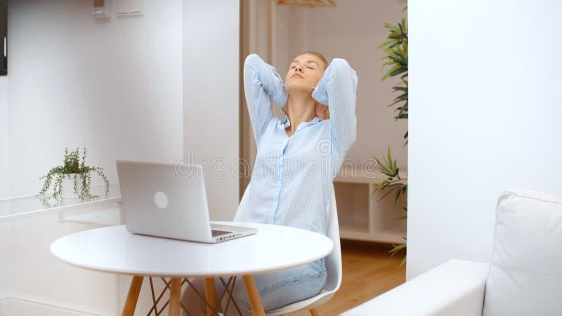 Mujer joven que trabaja en su ordenador portátil y que usa smartphone en casa fotos de archivo