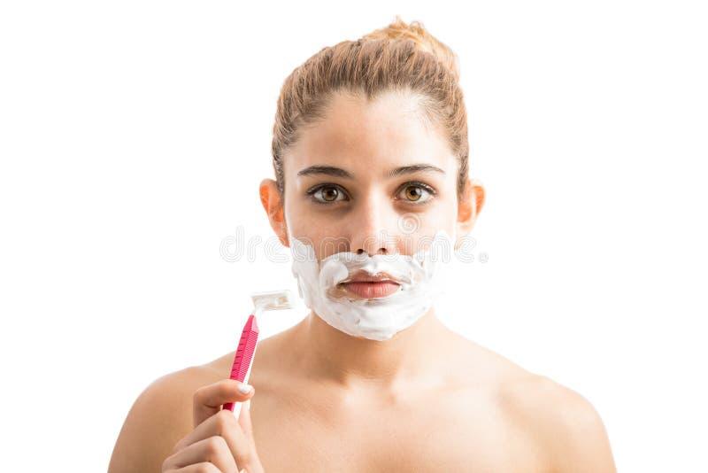 Mujer joven que trata del pelo facial foto de archivo libre de regalías