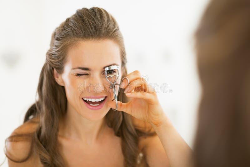 Mujer joven que usa el bigudí de la pestaña en cuarto de baño fotografía de archivo libre de regalías