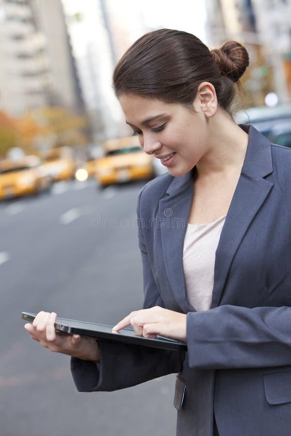 Mujer joven que usa el ordenador de la tablilla en New York City