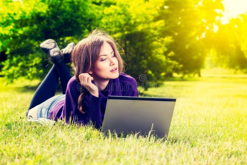 Mujer joven que usa el ordenador portátil en el parque que miente en la hierba verde fotos de archivo