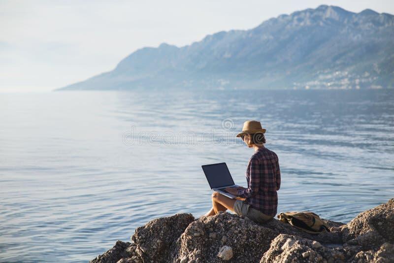 Mujer joven que usa el ordenador portátil en una playa Trabaja independientemente el concepto del trabajo imágenes de archivo libres de regalías