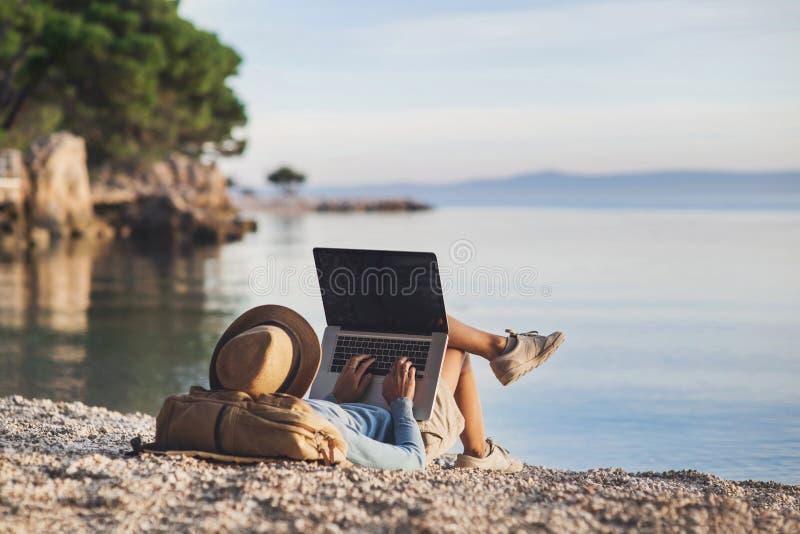 Mujer joven que usa el ordenador portátil en una playa Trabaja independientemente el concepto del trabajo imagen de archivo